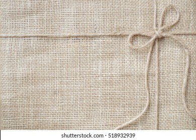 Burlap background tie with rustic burlap twine, natural product gift and eco-friendly concept.