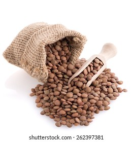 Burlap bag with lentils and wooden scoop on white background.