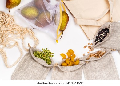 Burlap bags with grains and beans, linen bag and reusable bags with pears. Zero waste concept. White background. Copy space