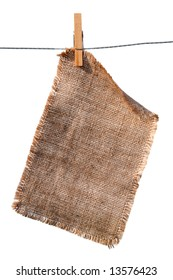 burlap canvas with lacerate edges hanging with wooden peg, isolated on white