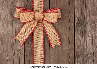 Burlap Christmas bow and ribbon side border, above view on a rustic wood background