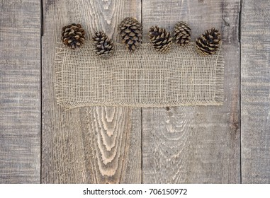 Burlap fabric with autumn pine cone border on rustic wood background. Top view with space for text