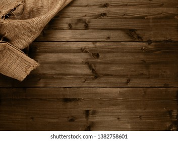 Burlap fabric cloth on brown wooden kitchen table with copy space