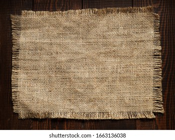 Burlap fabric on a brown wooden background. Copy space for text