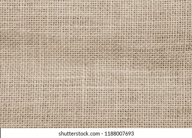 Burlap hessian jute sackcloth woven flax canvas texture background in sepia cream old aged brown color