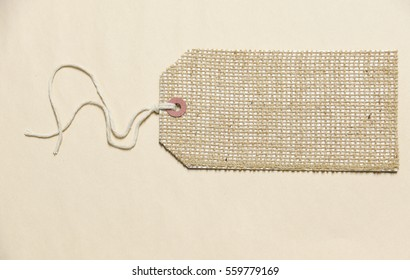 Burlap luggage tag or label with attached string on a tan paper background with lots of room for text