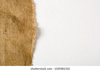 Burlap lying on a white wooden table. Preparation for the designer. Plenty of room for text and photo