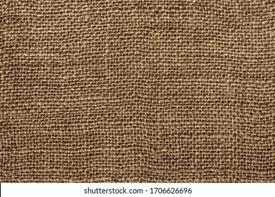 Burlap macro photo. The texture of the fibers and threads of coarse canvas. Seamless burlap texture.