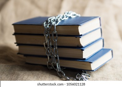 burlap on which lie forbidden books bound by a chain of metal
