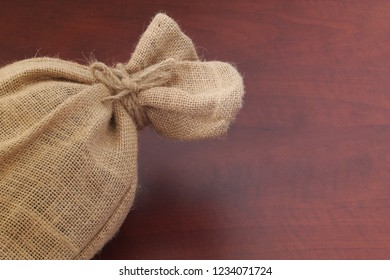 Burlap sack with jute rope close up on wooden board, space for text message