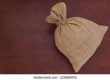Burlap sack with jute rope on wooden board with space for text