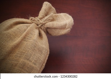 Burlap sack with jute rope on wooden table