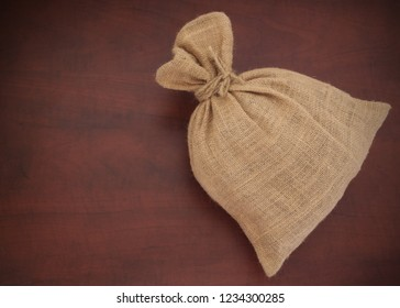 Burlap sack with jute rope on wooden board with copy space