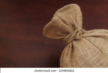 Burlap sack with jute rope on wooden board close up