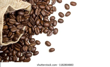 Burlap sack overflowing with coffee beans and into white surface background. With copy space.