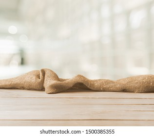 Burlap texture on wooden table on blurred background