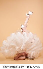 A burlesque dancer laying on the floor with an ostrich feather fan