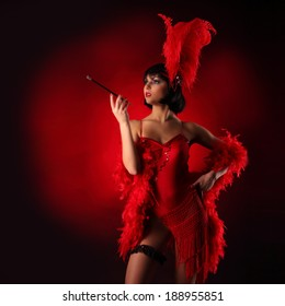 Burlesque dancer with red plumage and red short dress, black and red background