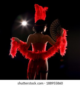 Burlesque dancer with red plumage and red short dress, black and red background, on the stage