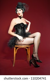 Burlesque pin up woman with black hair dressed in black. Sexy pose. Sitting on chair. Wearing black hat. Studio fashion shot isolated on red background.