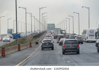 Burlington, Ontario, Canada - July 5, 2018:  Approaching James N. Allan Skyway over Burlington Bay, northbound on Queen Elizabeth Way highway, during rush hour on a rainy summer afternoon.
