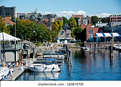 Burlington, VT, USA - September 30, 2013: People gather to watch the boats along the water at the Burlington Marina while pedestrians walk the Island Line Trail along the waterfront in the sun.