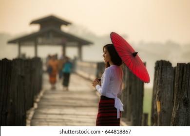 BURMA Portrait Beautiful Myanmar woman in Myanmar traditional dress holding red umbrella walking on the  U Bein Bridge in Mandalay Myanmar.