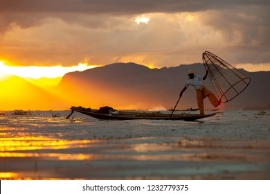 Burmese fisherman on bamboo boat catching fish in traditional way with handmade net.