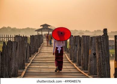 Une jeune Birmane tenant un parapluie rouge marchant sur le pont U Bein dans la matinée à Mandalay, Myanmar.
