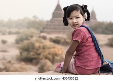 Burmese girl with traditional thanaka on pagoda blurred background at bagan in Mandalay, Myanmar