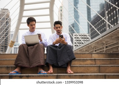 Burmese or Myanmar businessmen with longyi traditional dress working in Modern city. Fintech Foreign Business partner check plan and business news from smartphone. teamwork foreign business men.