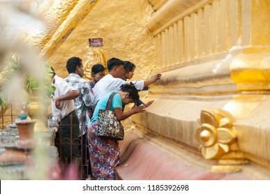 Burmese  people  putting gold leafs on the base of Shwezigon pagoda in Bagan. Bagan, Myanmar (Burma). 19 Apr. 2018.
