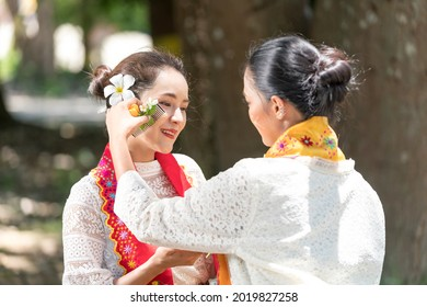 Burmese woman applying Tanakas powder. Southeast Asian young girls with burmese traditional dress visiting a Buddihist temple.