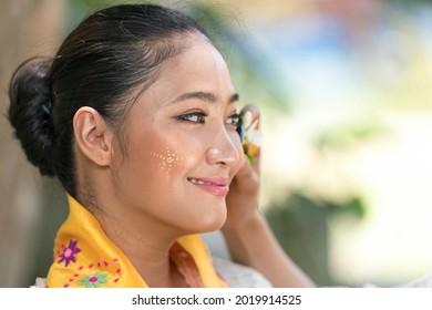 Burmese woman applying Tanakas powder.  Myanmar.