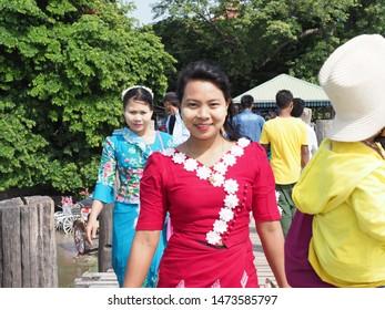 The Burmese woman ,มwearing red sarong , cultural cloth, smiling face, Tanaka makeup , natural products , walking on Upping bridge, Mandalay, Myanmar on 16 August 2019