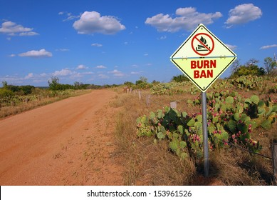 Burn Ban sign on dirt road through arid area of Central Texas Hill Country is symbolic of the serious lack of rain in the region.