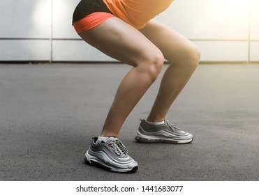 Burn in the buttocks. Side view of a young woman in sportswear doing squatting while standing outside on a gray background