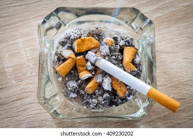 burn cigarette in a full ashtray