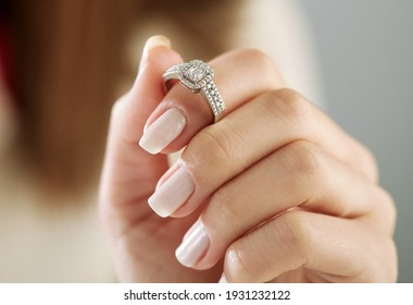 Burn an elegant diamond ring on the female finger. Love and wedding concept. Soft and selective focus.