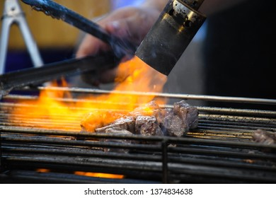 Burn the meat (Have fire) which is grilled on the charcoal stove.and The male hand holding a clamp. Street Food.Food that is not healthy