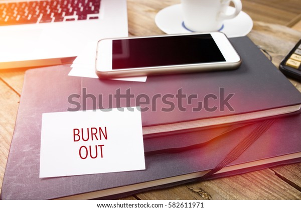 Burn Out on business card with text on office desktop with electronic devices, sun lit with lens flares.