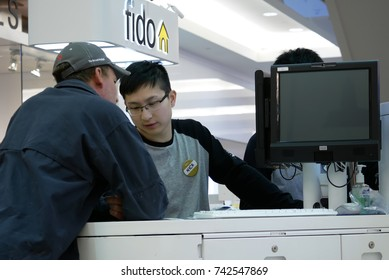 Burnaby, BC, Canada - April 03, 2017 : People asking fido sales clerk about cellphone plan inside Burnaby shopping mall