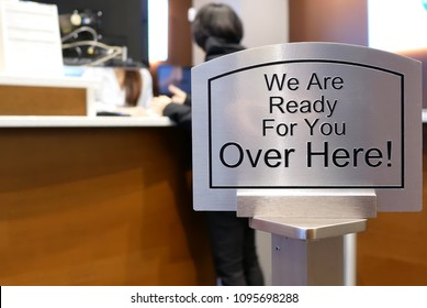 Burnaby, BC, Canada - April 09, 2018 : We are ready for you over here sign with blur motion people at service counter inside TD bank