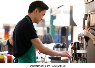 Burnaby, BC, Canada - May 04, 2017 : Motion of barista making coffee for customer at Starbucks store