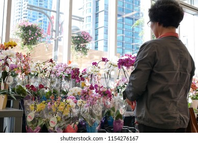 Burnaby, BC, Canada - May 30, 2018 : Motion of of people buying orchid on display flower rack inside price smart foods store