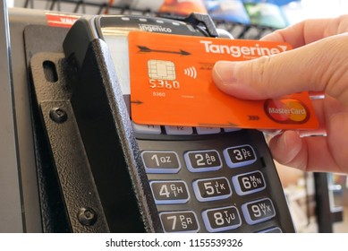 Burnaby, BC, Canada - May 30, 2018 : Close up of woman paying foods and tapping credit card at self-check out counter inside price smart foods store
