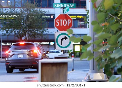 Burnaby, BC, Canada - May 30, 2018 : Motion of stop sign on sidewalk with blur traffic flow in Burnaby BC Canada