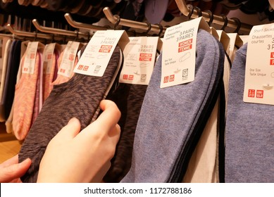 Burnaby, BC, Canada - May 30, 2018 : Motion of shopper buying socks at display socks cabinet inside uniqlo store