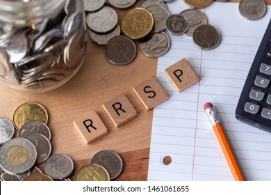 "Burnaby, British Columbia, Canada - July 20, 2019 - ""RRSP"" (Registered Retirement Savings Plan) spelled out in wooden letter tiles with money, pencil, paper, and calculator surrounding the word."