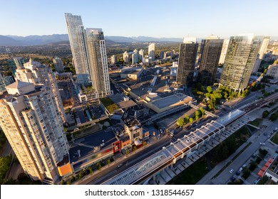 Burnaby, Greater Vancouver, BC, Canada -  July 12, 2018: Aerial view from above of Metrotown Skytrain Station and the Shopping Mall during a sunny sunset.